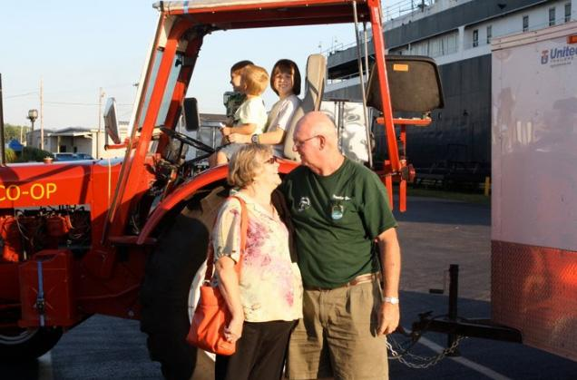 """Tractor Dave"" returns home in Ludington, MI after a 4,100 mile tractor ride through the Midwest. His grandchildren sit on the tractor and his wife ""Mrs. Tractor Deb"" welcomes him home."