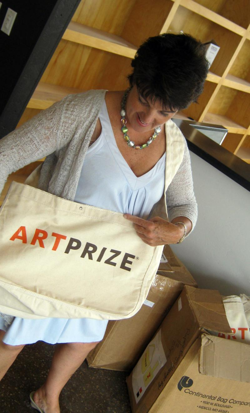 ArtPrize Executive Director Catherine Creamer shows off the ArtPrize totebag. The bag is one of at least 50 different pieces of ArtPrize swag available for purchase.