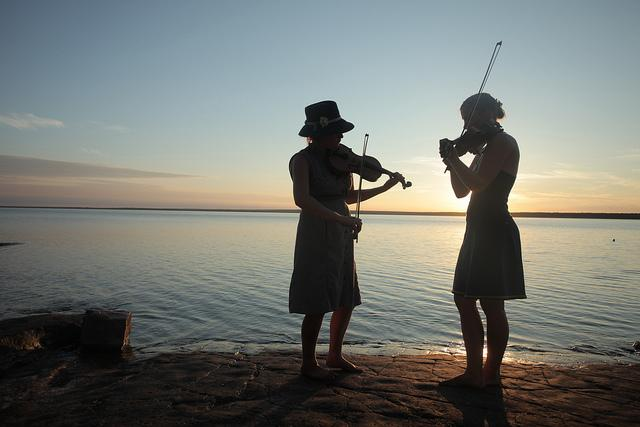 Two fiddle players perform on Rabbit Island as the sun sets