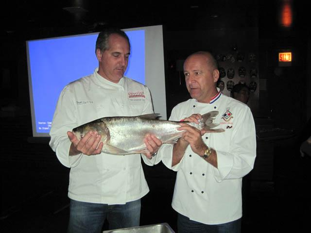 Chefs Tim Creehan (left) and Phillipe Parola with a bighead carp.