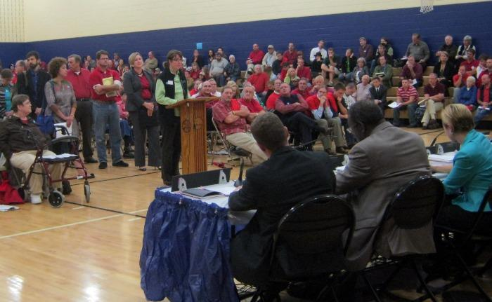 West Michigan Environmental Action Council Executive Director Rachel Hood addresses city commissioners at the public hearing Tuesday. Landlords against the changes are wearing red.