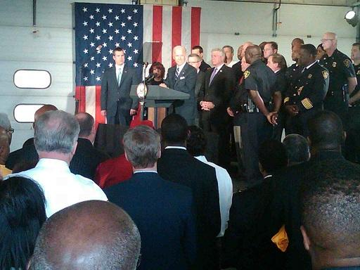 Vice President Joe Biden is flanked by Flint police officers and firefighters during a speech at one of the city's fire stations
