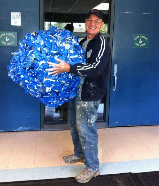 Paint for Kids founder Gene Firn after a painting project at Lawton elementary in Ann Arbor. The ball of tape measures 3 ft in diameter.