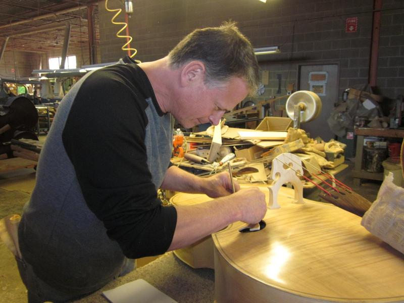 Tom Link, owner of Link Bass and Cello, glues a label into a finished bass violin in his factory.