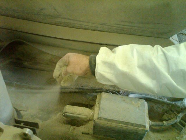 Dennis Brabant sifting the fine fly ash through his fingers inside the silo at the Eckert power plant.