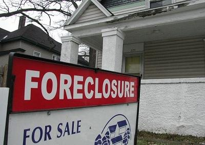 House with a foreclosure sign out front.