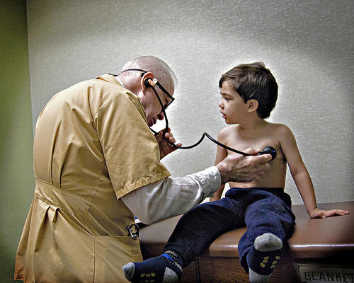 A doctor with a stethoscope on a young boys naked chest (he's wearing pants though)