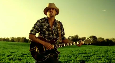 Kid Rock standing in a field playing a guitar