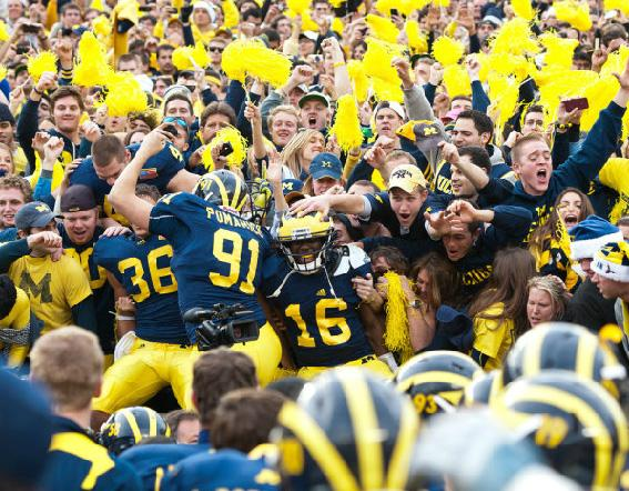 U of M quarterback Denard Robinson and other teammates celebrate their win over Ohio State with fans in the student section.