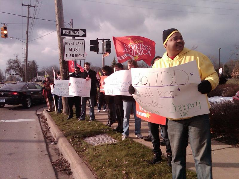 Protesters stand outside the Lansing office of Michigan Republican Congressman Mike Rogers