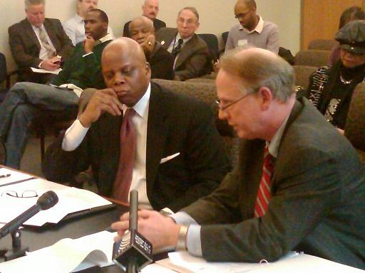 Highland Park school district financial director Randy Lane (left) listens as district counsel George Butler makes his arguments to a hearing officer in Lansing