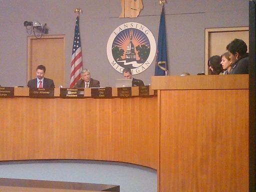 Lansing city council president Brian Jeffries (sitting in front of the US flag) precides over his first meeting of the council.