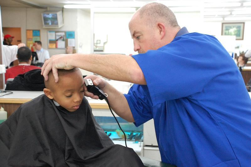 "For $2, this little guy gets a ""college boy"" cut from barber student Tom Amundson."