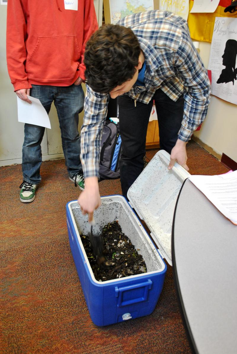 A presenter demonstrates how to start an indoor compost bin.