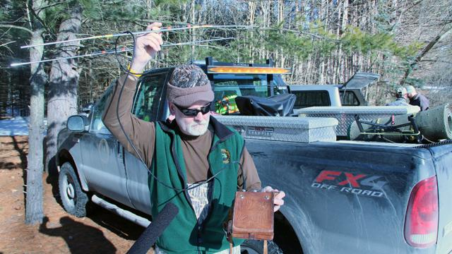 The DNR's Dan Moran checks to make sure the bear's new collar is working.