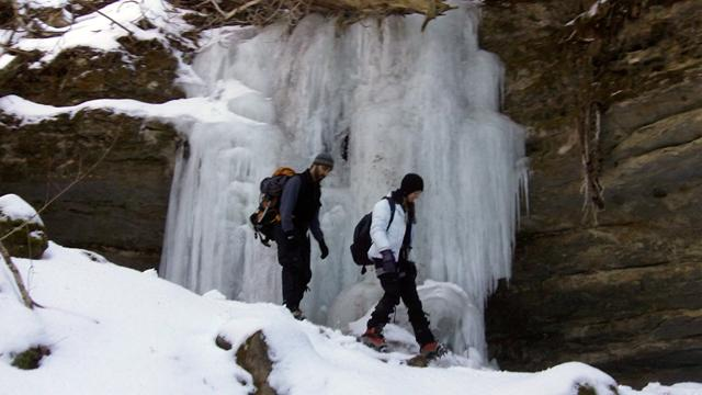 Neale Batra and Laura Haskins hike past a frozen waterfall at the Pictured Rocks National Lakeshore. Features like this can be found throughout the park.