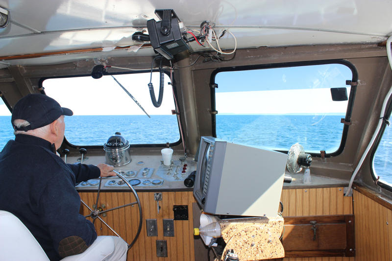 Don Kilpela at the helm of the Isle Royale Queen IV