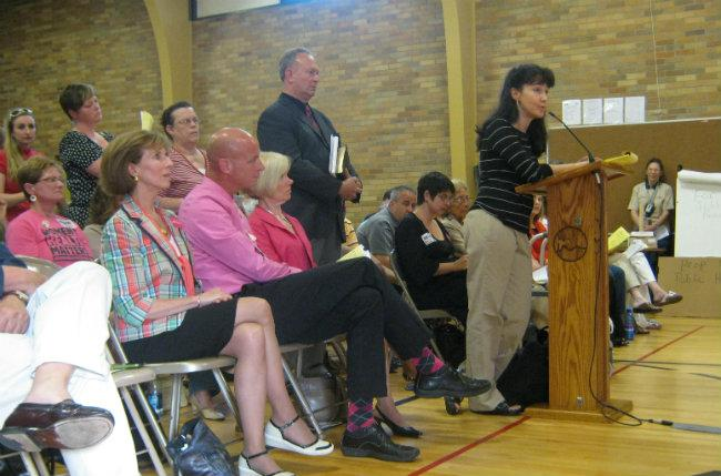 People line up to speak at city commission's 'night out' at Rosewood Elementary School's gym. Grand Rapids resident Adrienne Urban (at the podium) spoke in favor of the proposal.