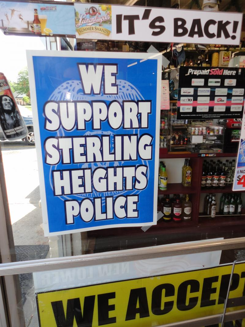 A sign in a Sterling Heights convenience store. The city had to cut police and firefighters for the first time this year.