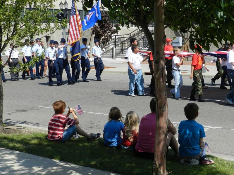 A family watches Lansing's Independence Day parade from a shady spot