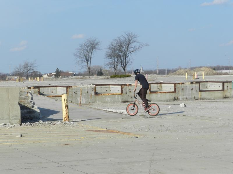 A cyclist rides on what had been the site of an auto plant in Lansing Township