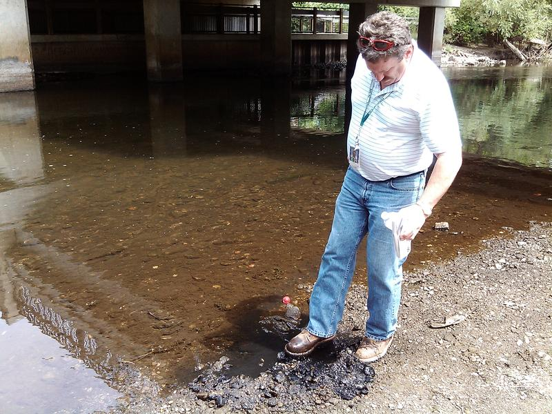 Kevin Lund, a senior geologist at the MDEQ's Department of Remediation, kicks over gravel to reveal the pollution along the Huron River.