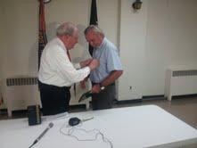 Senator Carl Levin, left, awards Arnold Spencer the Purple Heart.