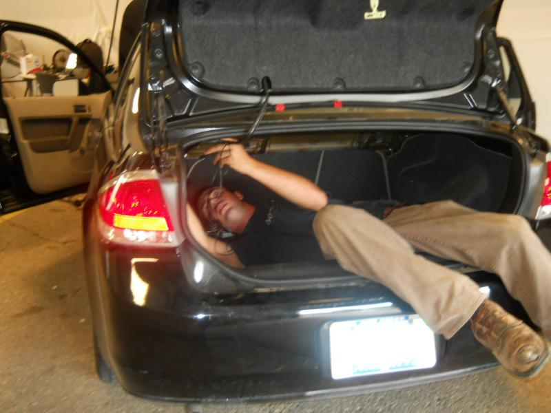 UMTRI technician Stan Baldiss installing a transmitter in a study participant's vehicle
