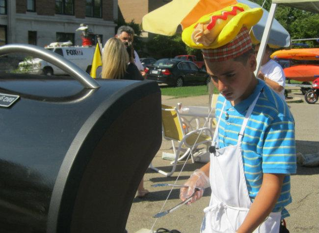 13-year old Nathan Duszynski grills hot dogs in downtown Holland Thursday.