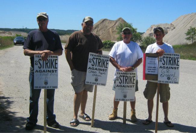 Bill Steckling (center right) and three other workers near the pit in Belmont. You can see the security worker's car in the background videotapping the men.
