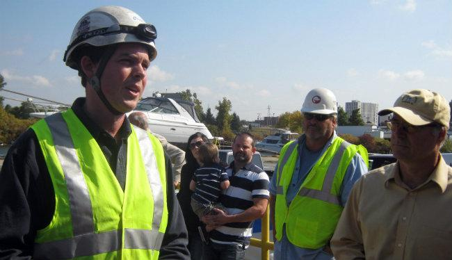 Devon Linehan (left) of Nordex, a wind turbine manufacturer, answers questions from people gathered to watch. Ed Hogan (middle in hard hat) and Max McKee (right) of Sand Products and The Mart Dock look on.