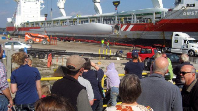 People come to The Mart Dock to watch the wind turbines come off the ship in Muskegon.