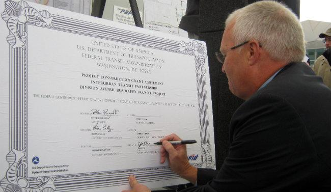 Wyoming Mayor Jack Poll adds his signature to a giant construction agreement for the Silver Line at a press conferece Thursday.