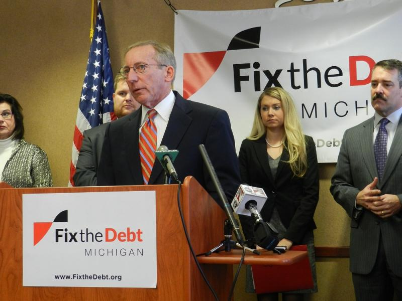 Ken Sikkema, senior policy fellow at Public Sector Consultants and former state senate majority leader, is the co-chair of the Fix The Debt committee.   He's speaking at a news conference in Lansing, flanked by other members of the committee