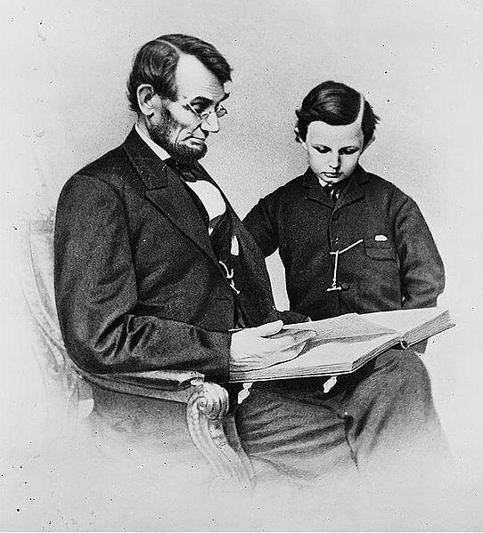 Abraham Lincoln and his son Tad looking at an album of photographs.