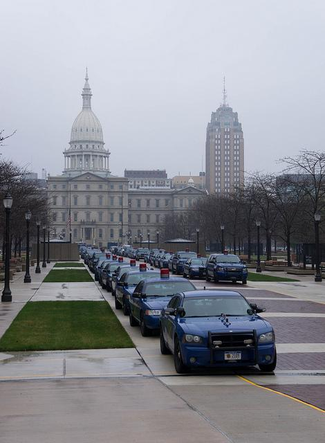 Police vehicles line up outside the state capitol during right-to-work protests