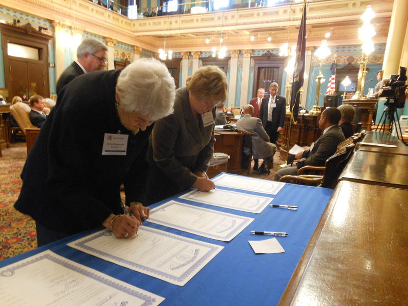Michigan Electoral College delegates Marion Vanderveen and Toni Sessoms signing documents to cast the state's 16 electoral votes for President Barack Obama and Vice President Joe Biden.