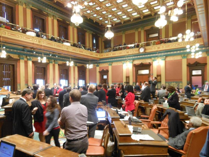"""House Democrats crowd around podium after the first """"right-to-work"""" bill passes, demanding a motion to reconsider. Motion was denied."""