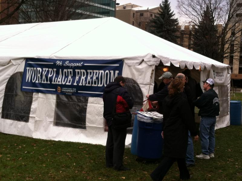 The group Americans for Prosperity pitched a tent on the lawn of the state Capitol as part of the lobbying effort in support of right-to-work.