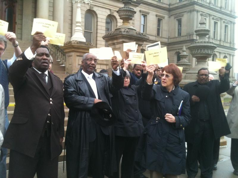 Michigan clergy members pray at thestate Capitol while holding cards with the names of children killed by gunviolence