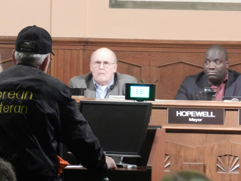 Kalamazoo Mayor Bobby Hopewell (right) and city manager Kenneth Collard listen as a city resident speaks during last night's city commission meeting