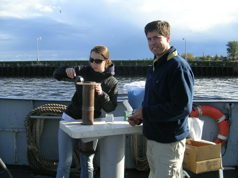 Professor Bill Arnold takes sediment samples with a student.