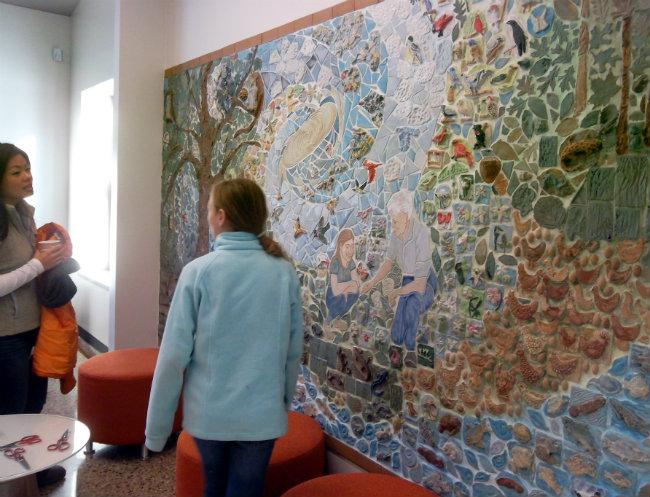 People check out a large mosaic on the wall in a common room at the new Blandford School.