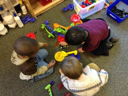 young kids playing with toys on floor