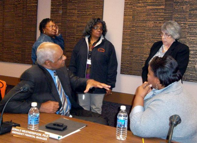 Don Weatherspoon answers questions from Mary Valentine (top right) after a school board meeting following the repeal of Public Act 4.