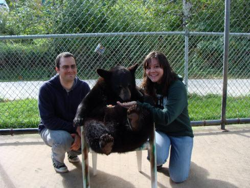A couple poses with a bear cub at Oswald Bear Ranch, Newberry, Michigan
