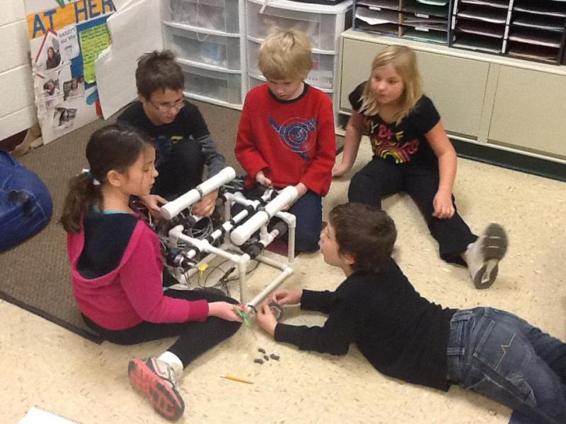 Heritage Exploratory Academy kids discussing their remote-operated vehicles