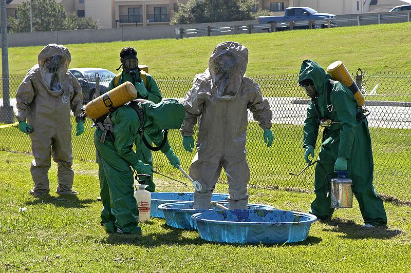 Members of an area Emergency Medical Technician team in Baton Rouge, Louisiana undergo training required for certification as rescue (grey suits) and decontamination (green suits) unit responders to hazardous material and toxic contamination situations.