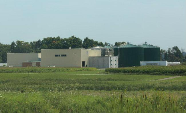 Two of the three large, green digester tanks are visable from a nearby road.