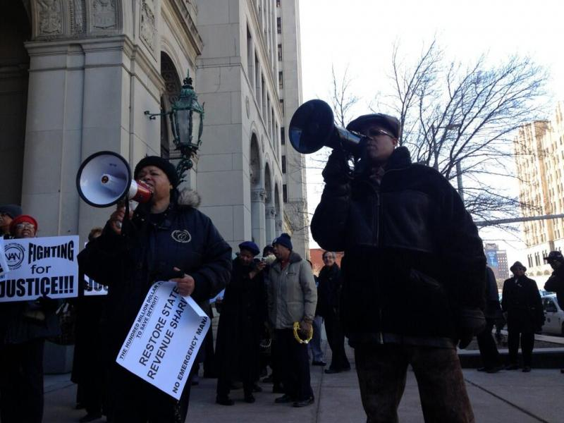 Outside Cadillac Place in Detroit. Protesters gather as Gov. Snyder announced EM choice.